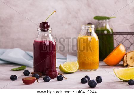 Assortment of bright smoothies with grapes, cherry, blueberry, tangerine and spinach over stone table