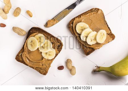Peanut butter sandwiches with banana slices. Top view. Space for text