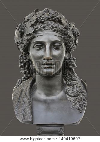 Ancient bronze statue of Dionysus isolated on a dark grey background. Dionysus is the Olympian God of the grape harvest wine and merriment. He was also known as Bacchus.