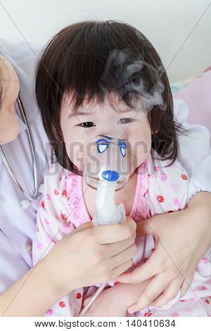 Closeup Asian Child Having Respiratory Illness Helped By Health Professional With Inhaler. Sad Girl