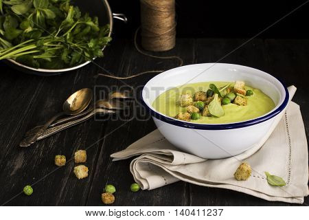 Green cream peas soup with croutons. Dark style. Selective focus. Space for text