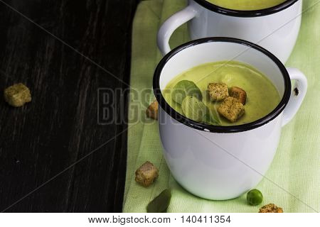 Green gazpacho cream soup with croutons in enamel mugs over dark wooden table. Natural light. Top view