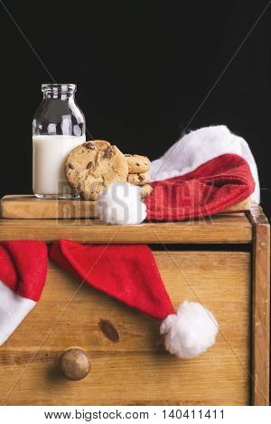Bottle of milk with straw and chocolate chips cookies for Santa. Xmas composition on old chest of drawers. Selective focus. Toned image