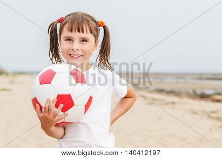 Little girl with pigtails proudly holds a soccer ball in his hands.