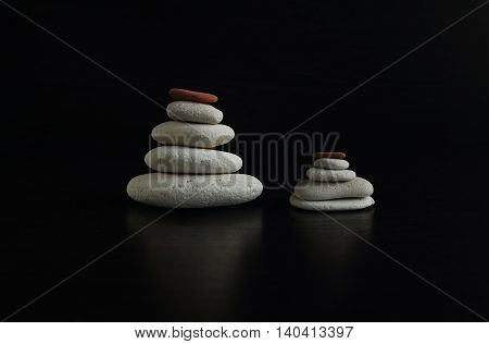a set of smooth stones on a black background, stacked in the order