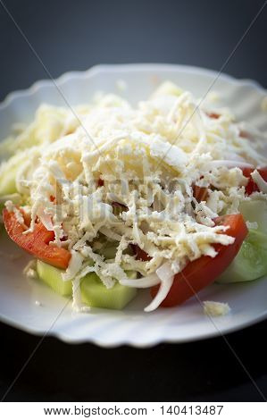 Traditional serbian salad on white plate on dark background.
