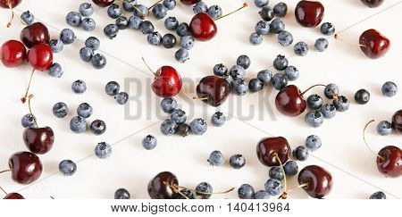 Fresh cherries and blueberryon a cloth from flax top view. Berry mix.