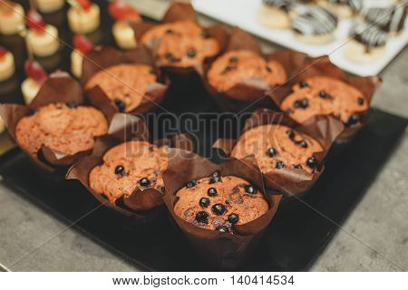 Freshly baked honey raisin muffins in rustic setting. Vintage pewter dishes with ingredients in background. Low key still life with directional natural lighting and shallow dof.