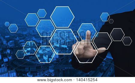Businessman hand pushing blank hexagon shape virtual technology screen over city tower and street blue tone