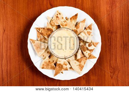 Delicious homemade nachos with spicy cheese sauce on a round white plate. Traditional Mexican food top view