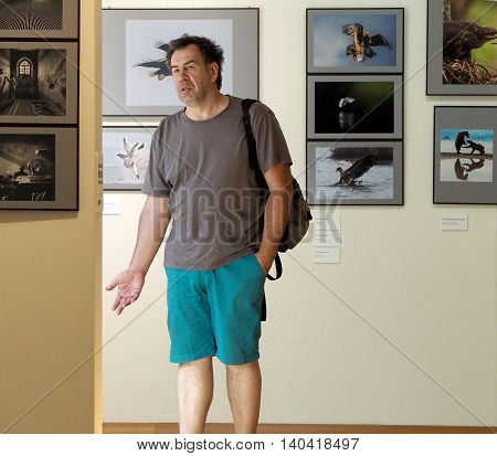 MOSCOW, RUSSIA - July 17, 2016: Mature adult man have a good look at photos. Classic Photo Gallery. Russian Week Of Photography 2016. July 17, 2016 in Moscow, Russia