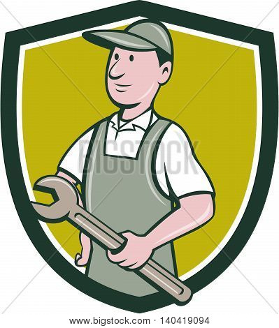 Illustration of a repairman handyman worker wearing hat and overalls holding spanner wrench looking to the side viewed from front set inside shield crest done in cartoon style.
