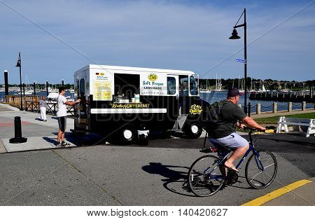 Newport Rhode Island - July 17 2015: Bicyclist passes Del's Soft Frozen Lemonade truck on the pier at Fort Adams State Park