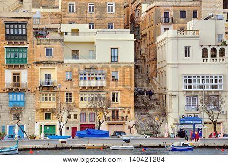 SENGLEA MALTA - MARCH 8: Traditional boats and cars on the waterfront of Senglea Isla on March 8 2013. Senglea is a small town in the Big Valletta city Malta.
