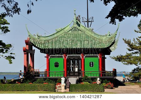 Newport Rhode Island - July 16 2015: The Chinese Tea house with ceremonial gate overlooks the sea on the grounds of 1892 Marble House