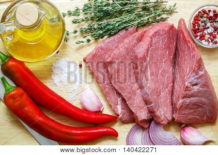 Raw meat vegetables and spices . Fresh beef peppers red onion garlic thyme olive oil. The ingredients for a tasty lunch