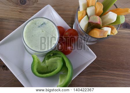 Useful summer snack: vegetables and yogurt sauce with herbs. Against the background of a rustic wooden table