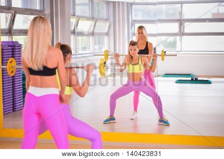 Sporty woman with barbell doing squats, instructor monitors the process.