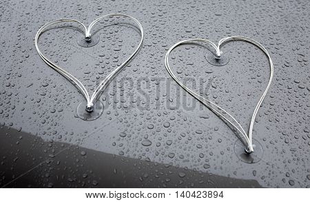 two hearts on the hood of a wedding carriage with raindrops