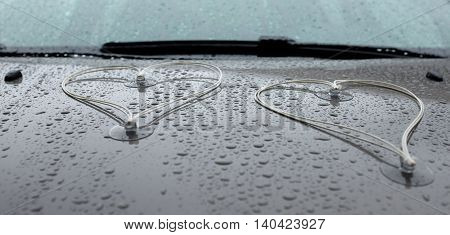 ​two hearts on the hood of a wedding carriage with raindrops