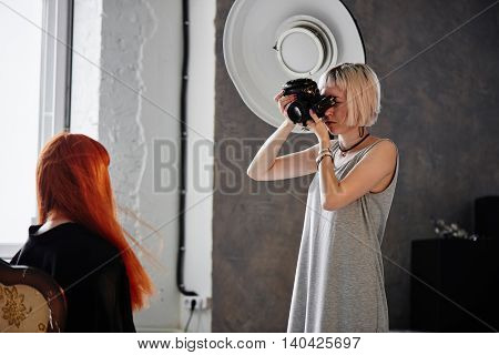 Girl photographer photographing fashion model in Studio in black