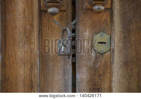 Old lock on a brown wooden cracked doors