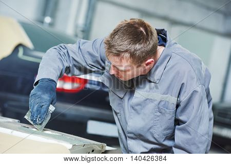 Repairman worker stopping car body before painting at garage