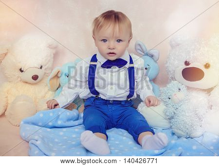Little baby boy in a white shirt blue pants suspenders and bow tie on background of toys. Stylish toddler in a fashionable bow-tie. Little gentleman. First year anniversary. Toned image.