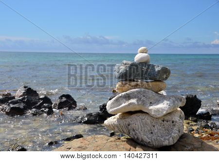A stack of rocks in a Zen pattern with the Atlantic Ocean in the background