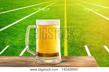 Glass of beer on football field stadium background