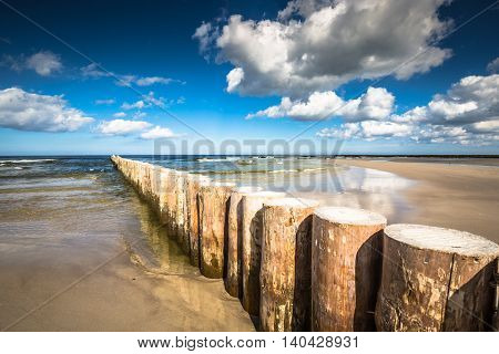 Wooden breakwaters on sandy Leba beach in late afternoon Baltic Sea Poland