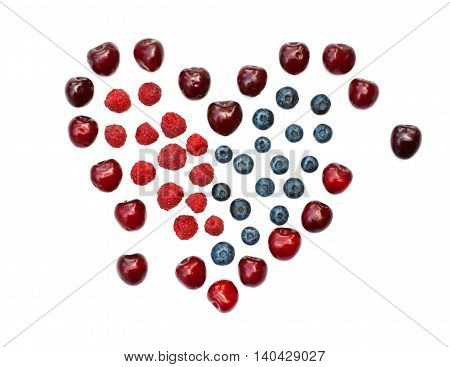 Isolated heart of cherry, blueberry and raspberry on a white background
