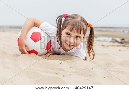 Little girl with pigtails lying on the sand to catch a soccer ball.