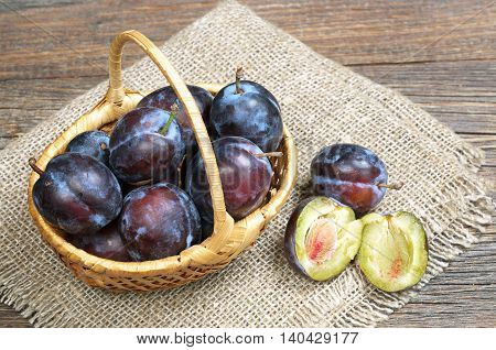 Ripe plums in basket on wooden table with rough cloth