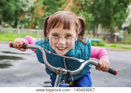 Portrait of a playful funny girl on her bike.