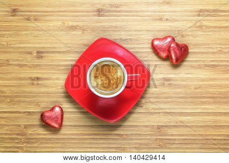 Heart shaped sweets wrapped in a bright red foil lying on a wooden texture with red cup of coffe near it. Background for romantic themes.