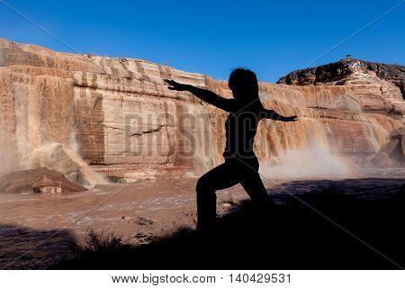 a woman practicing yoga at scenic grand falls in northern arizona