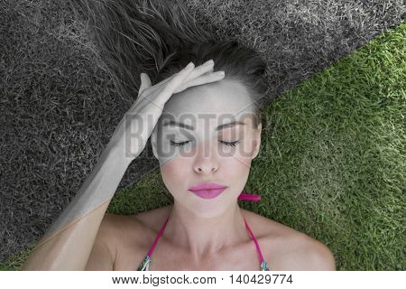 Closeup of woman with headache lying on a green grass on a sunny day