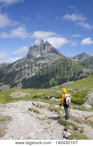 girl hiking with the Midi d'Ossau peak behind in France