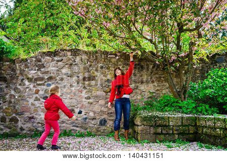 Mother With Little Daughter Playing With Falling Petals Spring Day