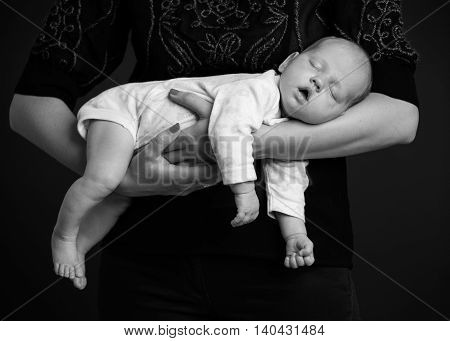 Woman holding a newborn on the hands baby is sleeping black and white