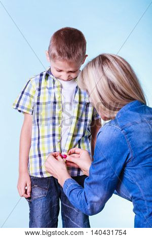Fitting garment for kids dress up help from parents. Mother help her son fasten buttons try new clothes prepare for leaving.