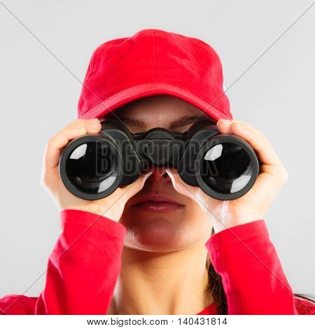 Accident prevention and water rescue. Closeup girl in red lifeguard outfit on duty looking through binocular on gray