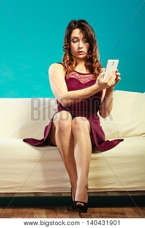 Technology internet and happiness concept. Young woman fashionable girl taking self picture selfie with smartphone camera while sitting on sofa at home