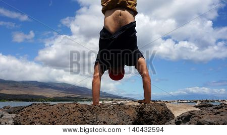 Man Handstands on Lava rocks of Molokai Harbor in the state of Hawaii.