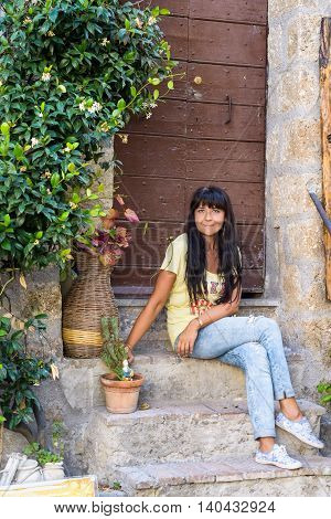 nice girl posing sitting in an ancient village called Calcata Italy
