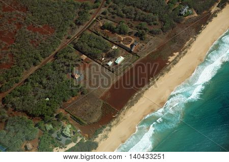 Aerial of Northwest coast of Molokai with waves crashing into Papohaku Beach and surrounding area of island with homes roads largely undeveloped. April 2016.