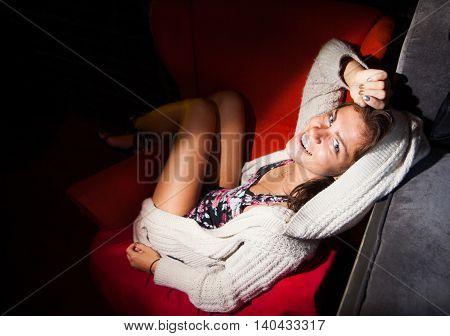 model in red armchair in black interior