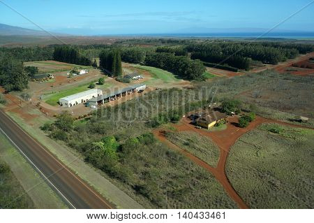 Aerial of Farm fields and equipment running to the ocean and Maui in the distance on Molokai Hawaii. April 2016.