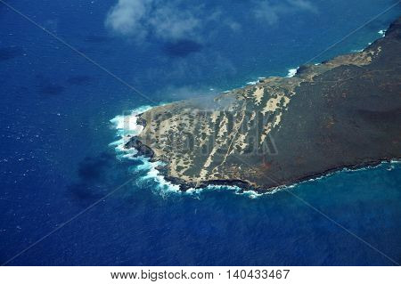 Aerial of Ilio Point on the Northwest coast of Molokai with waves crashing into shore and clouds in the air largely undeveloped. April 2016.